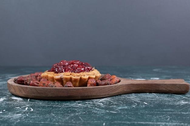 Bolo torta na placa de madeira com frutos de rosa secos.