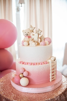 Bolo twotier branco rosa com número um, ursinho, bolas brancas e rosa e estrelas douradas em uma mesa com uma toalha de mesa cintilante para uma menina em seu primeiro aniversário.