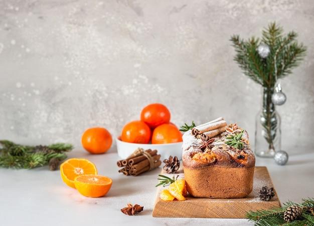 Bolo úmido de pão cítrico decorado com tangerinas, alecrim, especiarias e açúcar em pó. conceito de feliz natal e feliz ano novo.