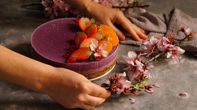 Bolo vegano cru com frutas e sementes, decorado com flores