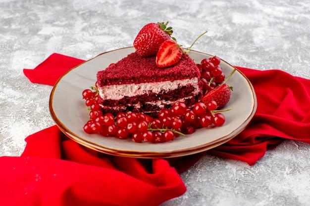 Bolo vermelho fatia de bolo de frutas de vista frontal dentro do prato com cranberries frescas e morangos alogn com tecido vermelho em cinza