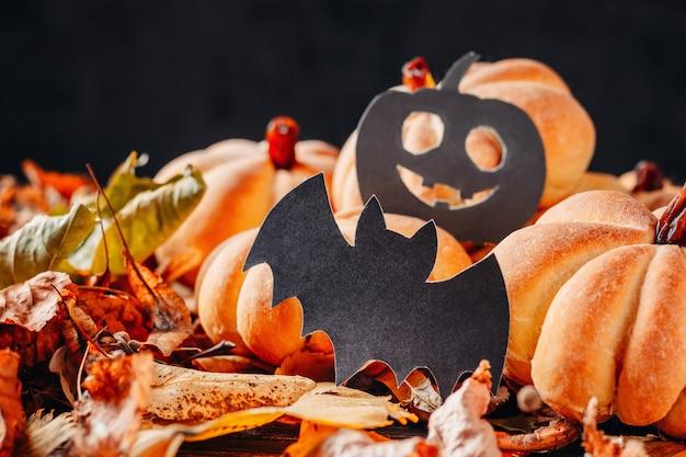 Bolos caseiros em forma de abóbora de halloween com folhas de outono em um escuro