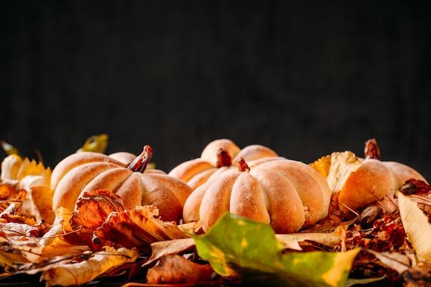 Bolos caseiros em forma de abóbora e folhas de outono no escuro com espaço de cópia. cozinhando para o halloween