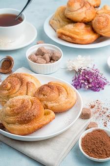Bolos caseiros, pãezinhos de caracol com açúcar em um fundo azul suave.