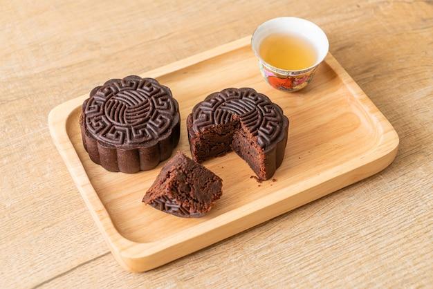 Bolos chineses de lua com sabor de chocolate amargo em prato de madeira