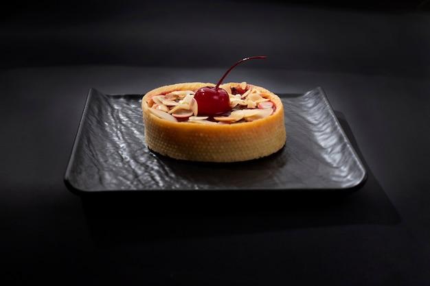 Bolos com cerejas por cima em prato preto