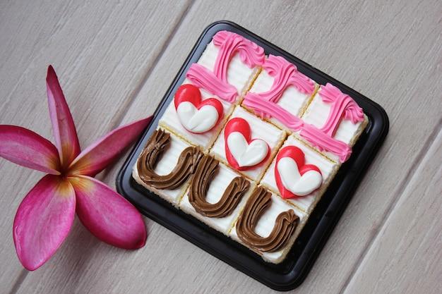 Bolos com corações de creme e uma flor de frangipani. a escrita eu te amo em bolos.