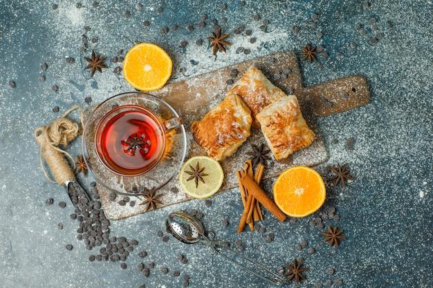 Bolos com farinha, chá, laranja, chips de chocolate, temperos vista superior em estuque e tábua de cortar