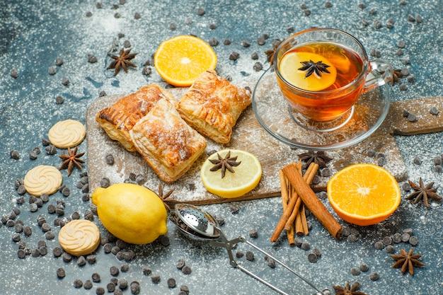 Bolos com farinha, chá, laranja, limão, biscoitos, chips de chocolate, especiarias, vista de alto ângulo em estuque e tábua de cortar