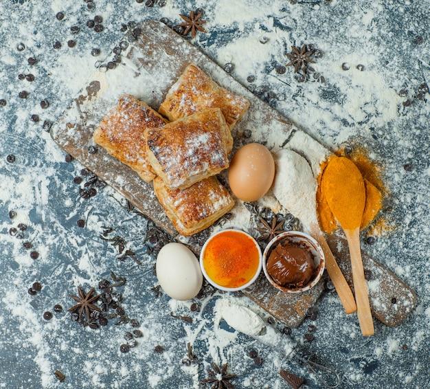 Bolos com farinha, chocolate, especiarias, ovos no concreto e tábua de cortar