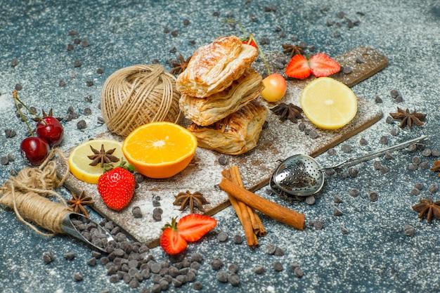 Bolos com farinha, frutas, chips de chocolate, especiarias, vista de alto ângulo de bola de linha em estuque e tábua de cortar