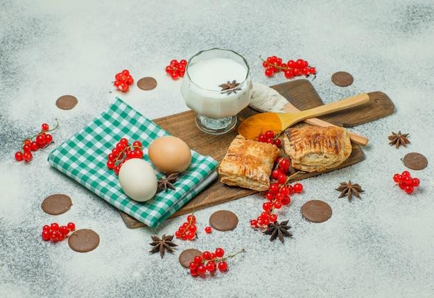 Bolos com farinha, groselha, leite, ovos, especiarias, biscoitos, visão de alto ângulo no concreto e na tábua de corte
