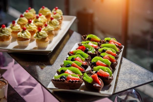 Bolos com frutas frescas e frutas na mesa de férias