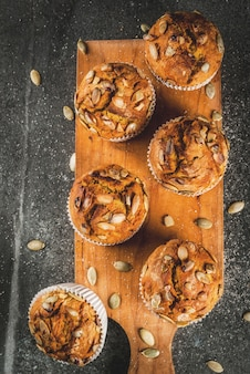Bolos cozidos no outono e inverno muffins de abóbora saudáveis com especiarias tradicionais da queda sementes de abóbora mesa de pedra preta