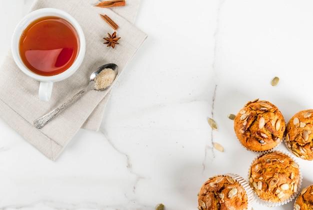 Bolos cozidos no outono e inverno muffins de abóbora saudáveis com especiarias tradicionais do outono sementes de abóbora com uma xícara de chá mesa de mármore branco