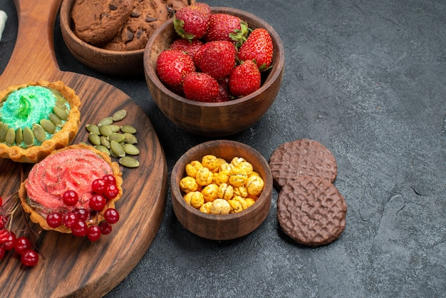 Bolos cremosos de vista frontal com frutas e biscoitos em fundo escuro