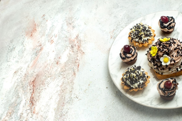 Bolos cremosos deliciosos com casca de chocolate na superfície branca bolo biscoito biscoito chá doce creme de frente