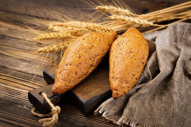 Bolos da farinha integral com a adição de sementes de linho em um fundo de madeira.