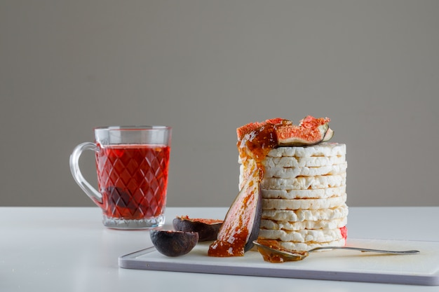 Bolos de arroz com figos, geléia, chá, colher de chá na tábua em branco e cinza,