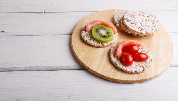 Bolos de arroz com salmão, kiwi e tomate cereja na mesa de madeira branca.