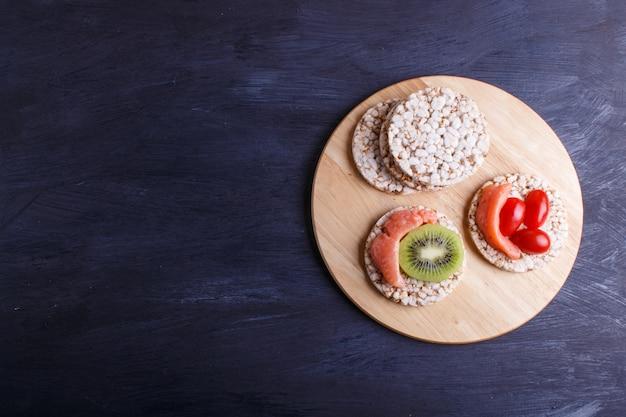 Bolos de arroz com salmão, kiwi e tomate cereja no fundo escuro de madeira.