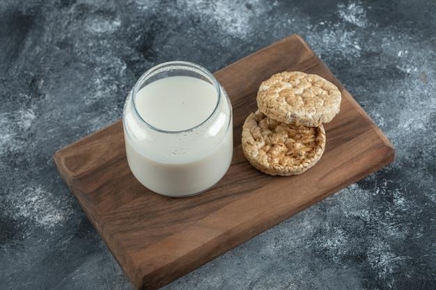 Bolos de arroz e copo de leite na tábua de madeira