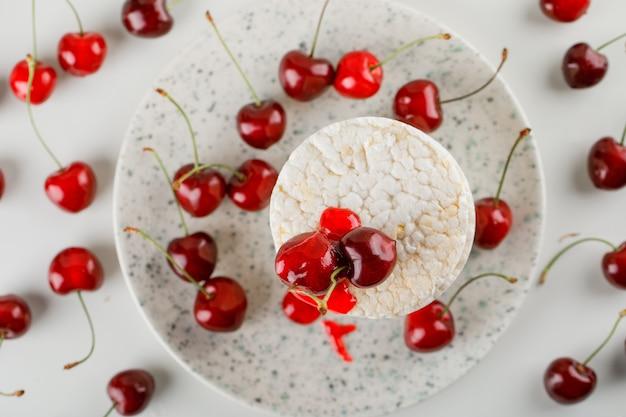 Bolos de arroz em um prato com cerejas, geléia