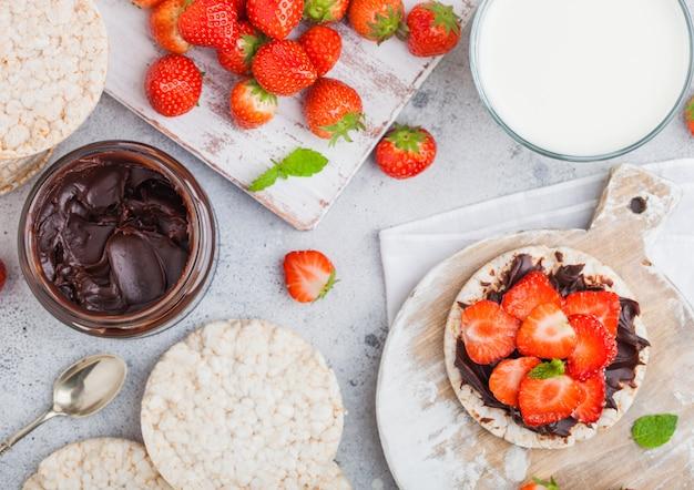 Bolos de arroz orgânicos saudáveis com manteiga de chocolate e morangos frescos na placa de madeira e copo de leite