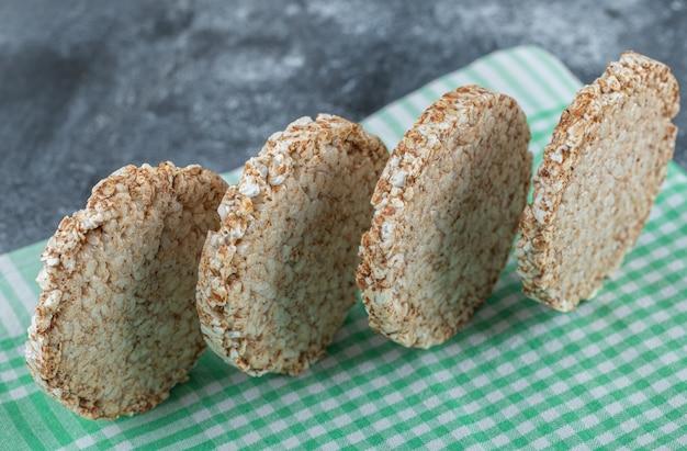 Bolos de arroz redondos dietéticos na toalha de mesa listrada.