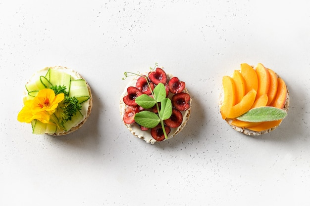 Bolos de arroz tufado com diferentes coberturas de frutas e vegetais em lanches veganos brancos