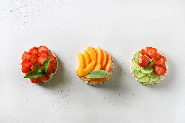 Bolos de arroz tufado com diferentes coberturas friuts e vegetais em branco. lanches veganos.