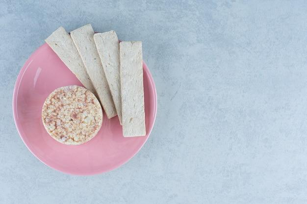 Bolos de arroz tufado e bolacha doce no prato em mármore.