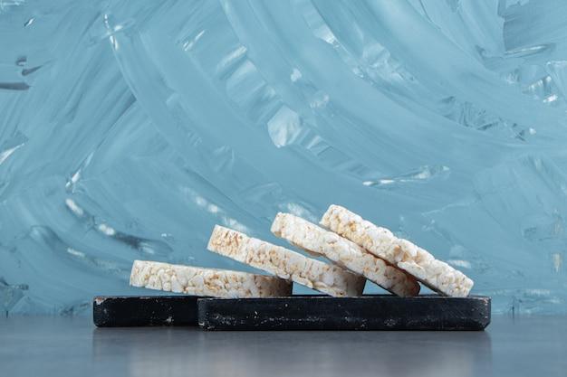Bolos de arroz tufado em uma placa de madeira escura.