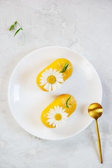 Bolos de caju de espinheiro-mar crus decorados com camomila em um prato branco.