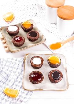 Bolos de chocolate pequenos com molho de leite, morango, chocolate e laranja no fundo da mesa de madeira branca.