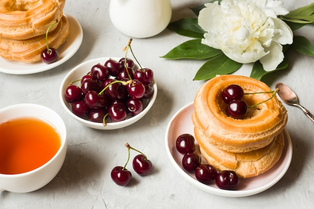 Bolos de creme anel com cereja em um prato em cinza
