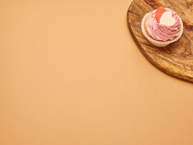 Bolos de cupcakes rosa com corações em uma placa de madeira de cozinha em um fundo marrom bege