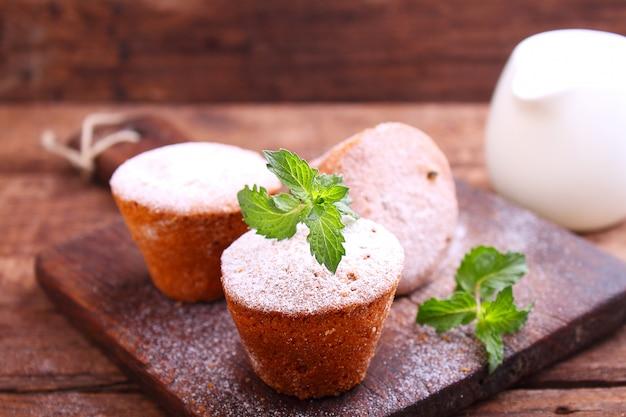 Bolos de esponja com passas decorados com açúcar em pó e folhas de hortelã