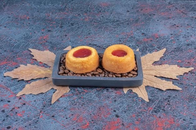 Bolos de geléia e grãos de café em uma pequena bandeja na mesa abstrata.