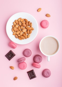 Bolos de macaron ou macaroon roxo e rosa com xícara de café e amêndoas