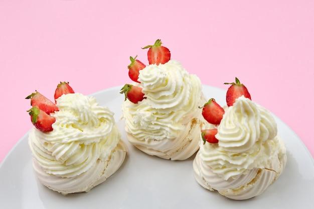 Bolos de merengue com creme de morango e chantilly em um prato em um fundo rosa