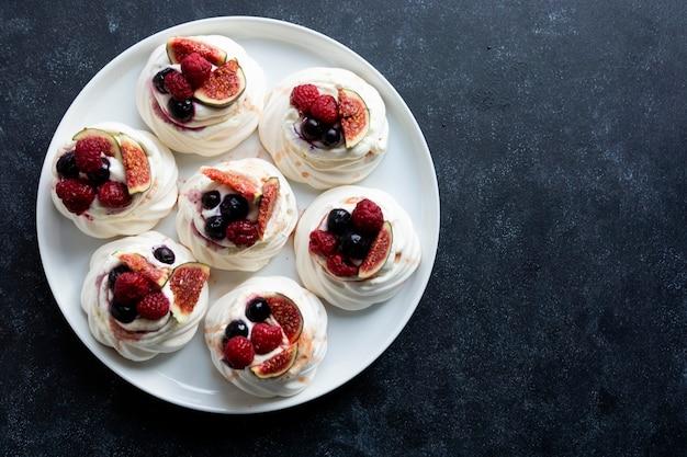 Bolos de merengue mini pavlova com frutas vermelhas e figo fresco