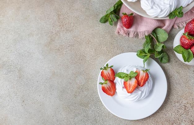 Bolos de merengue mini pavlova com morangos e hortelã em um fundo de placa de concreto