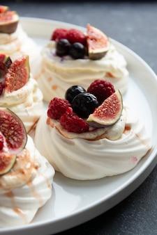 Bolos de merengue mini pavlova decorados com frutas vermelhas e figo