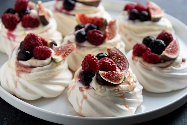 Bolos de merengue mini pavlova decorados com frutas vermelhas e figos