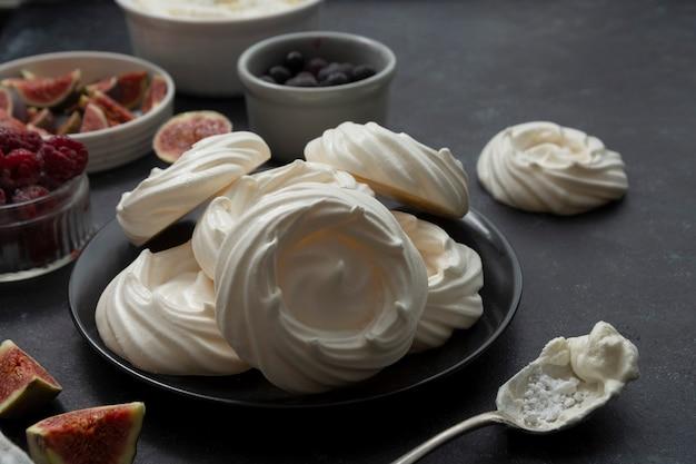 Bolos de merengue pavlova decorados com frutas vermelhas e figos