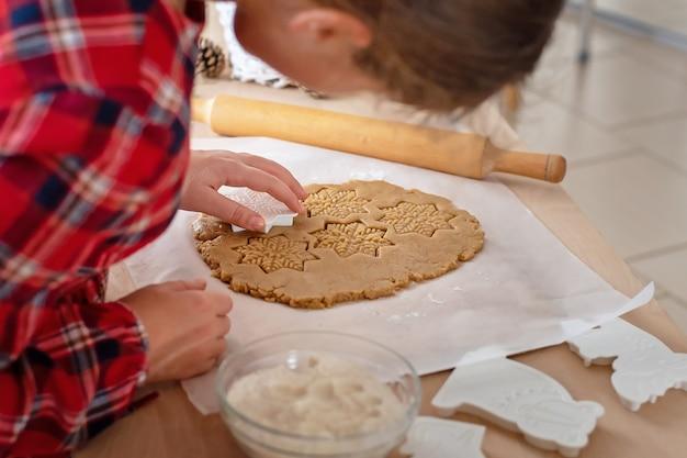 Bolos de natal. a garota faz pão de gengibre. detalhe da mão.