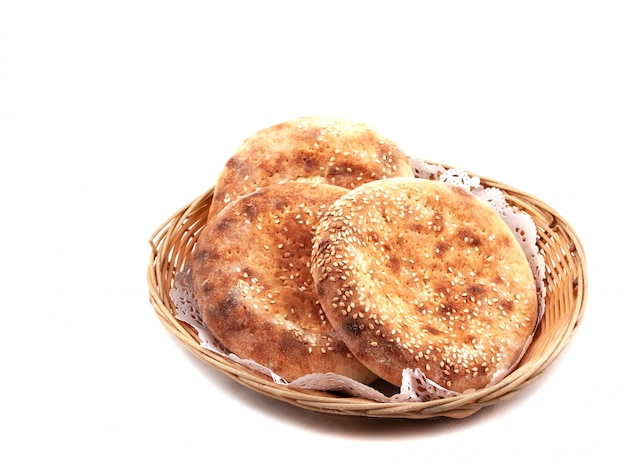 Bolos de pão com sementes de gergelim em uma cesta em um fundo claro