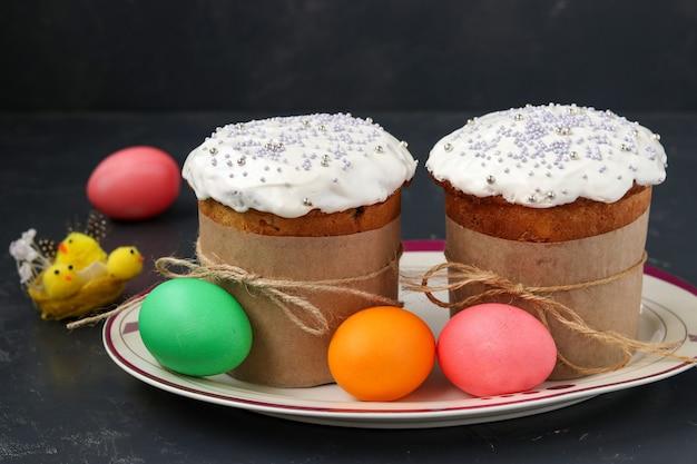 Bolos de páscoa e ovos coloridos estão localizados em um prato em um fundo escuro, foto horizontal