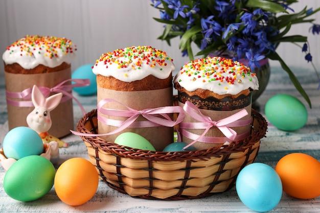 Bolos de páscoa e ovos coloridos para um feriado de primavera em uma cesta de vime sobre fundo azul